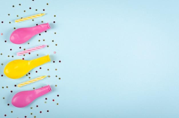 Farbige konfetti- und luftballonzusammensetzung auf blauer hintergrund-, partei- und feierdekoration.