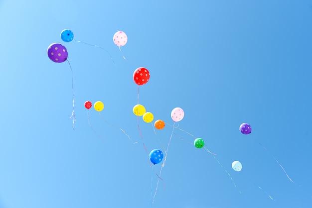Farbige luftballons fliegen in den blauen himmel