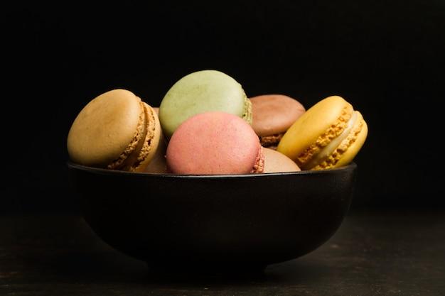 Farbige macarons in einer schwarzen schüssel