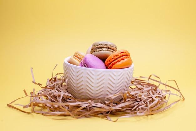 Farbige makronenplätzchen, die auf einem niedlichen weißen teller auf einem strohhalm liegen. dekoration wie das vogelnest und eier. ostern.