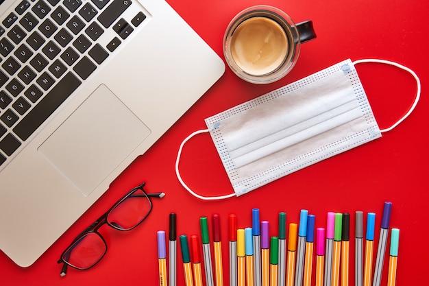 Farbige markierungen, maske und laptop auf dem schreibtisch