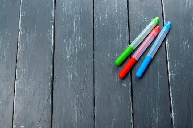 Farbige markierungsstifte auf hölzernem hintergrund