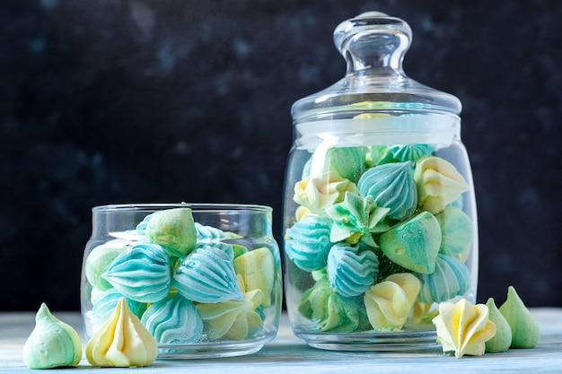 Farbige meringues in einem glasgefäß auf einem dunklen hintergrund