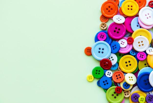 Farbige nähknopfzusammensetzung auf grünem pastellhintergrund. flach mit kopierraum liegen.
