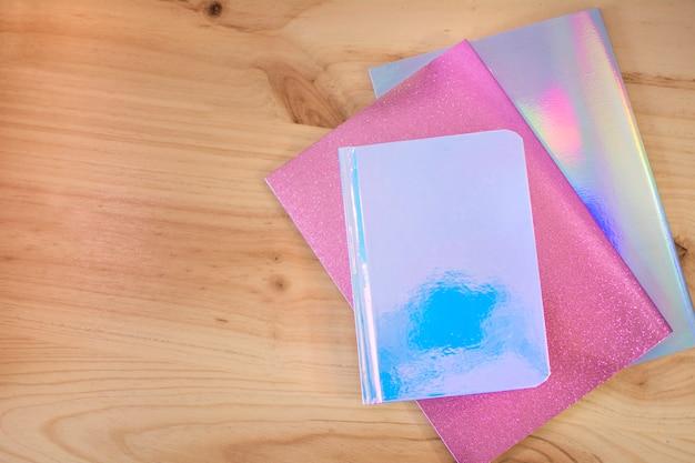 Farbige notizbücher auf hölzernem schreibtisch