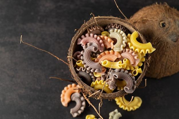 Farbige nudeln in form von handgemachten jakobsmuscheln in einer kokosnussplatte auf einer grauen vintage-wand, draufsicht