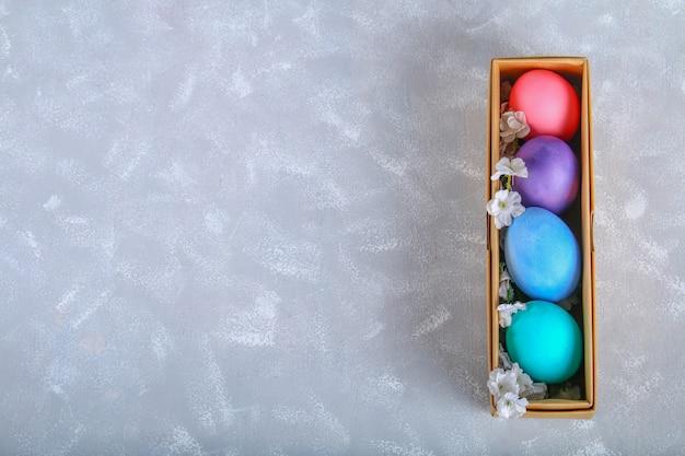 Farbige ostereier in einer geschenkbox auf einem grauen konkreten hintergrund.