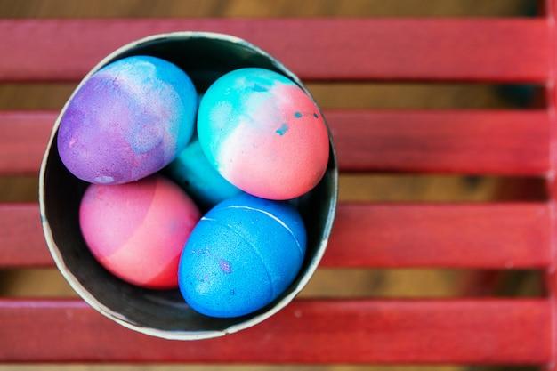 Farbige ostereier in einer keramikschale auf rotem hintergrund. bunte festliche helle eier abstrakt blau, rosa, grün und lila gemalt.