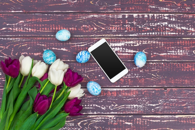 Farbige ostereier, tulpenblumen und smartphone