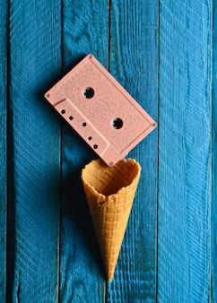 Farbige pastell-audiokassette und leeres waffelhorn auf einem blauen holztisch. draufsicht, minimalistischer trend, kreatives layout