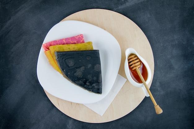 Farbige pfannkuchen mit honig