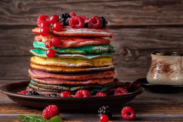 Farbige pfannkuchen mit obst, mandeln und puderzucker.