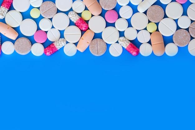 Farbige pillen auf blauem grund.