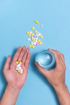 Farbige pillen in der hand mit wasser auf blauem hintergrund.