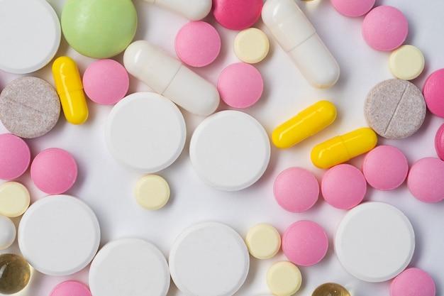 Farbige pillen, tabletten und kapseln auf weißer oberfläche