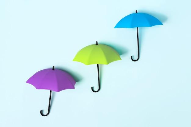 Farbige regenschirme auf blauem grund. konzeptualität und platz für den text