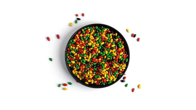 Farbige schokoladensonnenblumenkerne in der schwarzen platte isoliert.