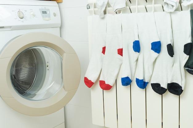 Farbige socken trocknen am heizkörper neben der waschmaschine. konzept der hausarbeit.