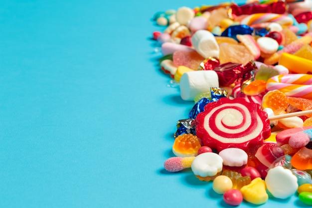 Farbige süßigkeiten auf blauem hintergrund
