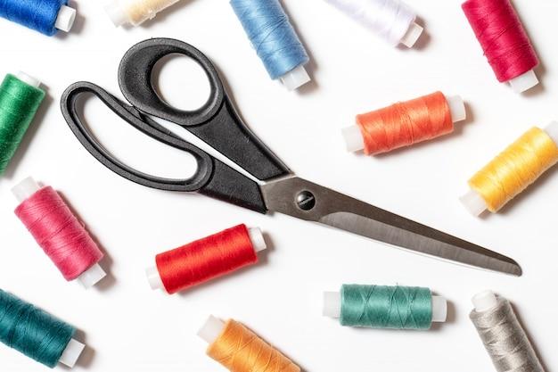 Farbige threadspulen und -scheren auf weißem hintergrund, nähendem, handgemachtem und diy-konzept