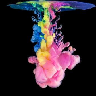 Farbige tinten in wasser auf schwarzer oberfläche