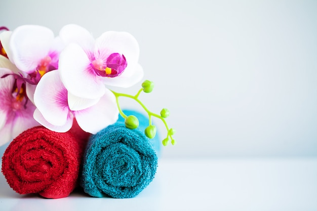 Farbige tücher und orchidee auf weißer tabelle mit kopienraum auf badezimmerhintergrund.