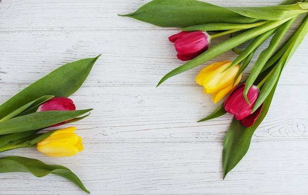 Farbige tulpen auf einem weißen hölzernen hintergrund.