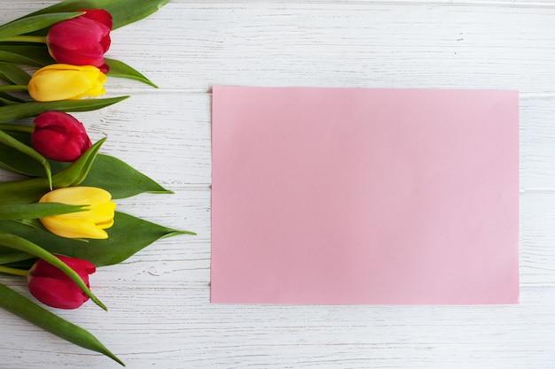 Farbige tulpen und weißer hölzerner hintergrund. das konzept gratuliert