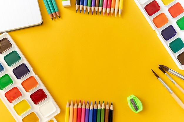 Farbige und einfache stifte, radiergummi, farben, pinsel, anspitzer auf einem gelben hellen hintergrund.