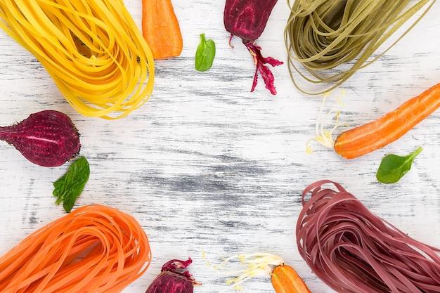 Farbige vegetarische teigwaren des rohen gemüses mit roten rüben, karotten und spinat. flach liegen.