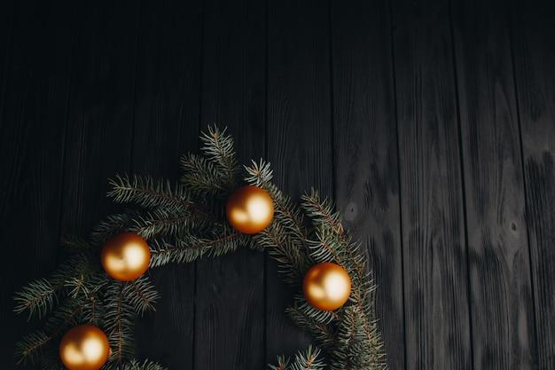 Farbige weihnachtsdekorationen auf schwarzem holztisch. weihnachtsbälle auf hölzernem hintergrund.