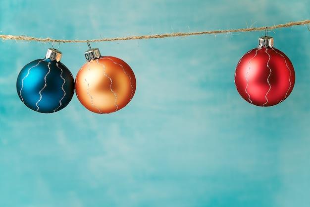 Farbige weihnachtskugeln, die am blau hängen