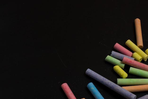 Farbige zeichenstifte auf einem tafelhintergrund.