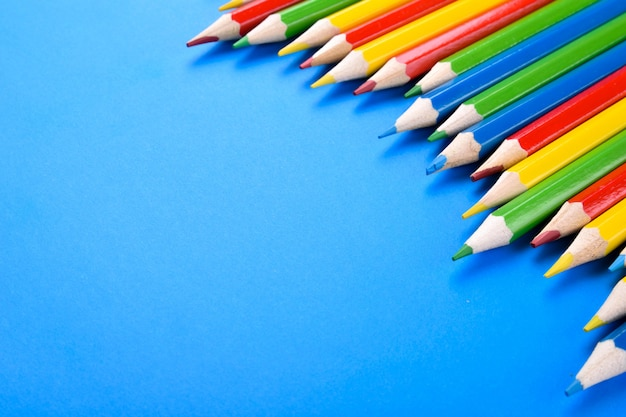 Farbiger bleistifthintergrund. farbbleistifte auf blau