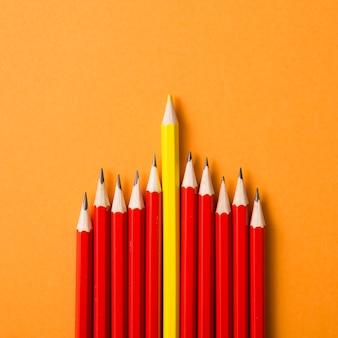 Farbiger gelber bleistift zwischen den roten bleistiften auf einem orange hintergrund