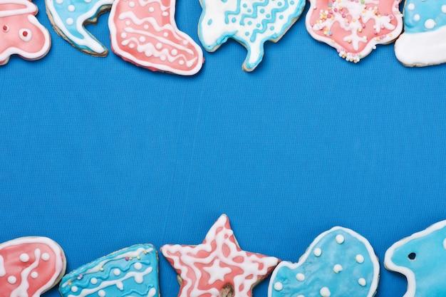 Farbiger glasierter weihnachtslebkuchen auf blauem hintergrund