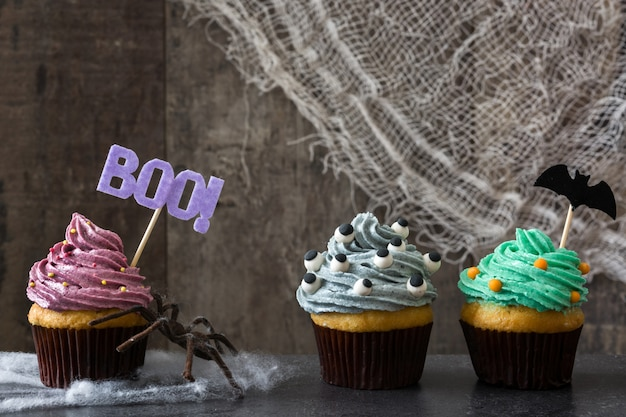 Farbiger halloween-kleiner kuchen auf schwarzem hintergrund. kopieren sie platz