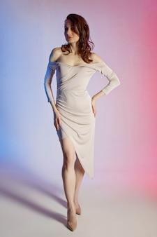 Farbiger hintergrund, neonlichter, studioaufnahme. modeporträt einer jungen eleganten brunettefrau.
