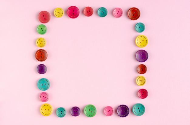 Farbiger nähender knopfzusammensetzungsrahmen auf rosa hintergrund.