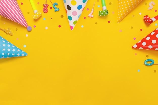Farbiger partyhut und kerzen, die auf gelbem hintergrund liegen.