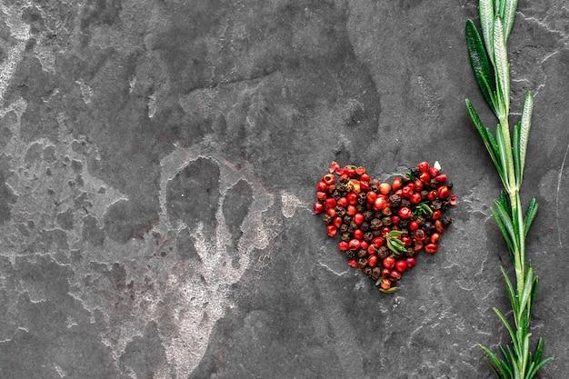 Farbiger pfeffer mit liebe zum grill auf stein, das herz der köchin, ein symbol der liebe.