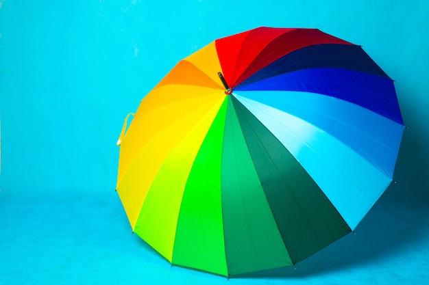 Farbiger regenschirm auf blauem hintergrund. heller regenschirm. speicherplatz kopieren. artikel über den schutz vor regen.