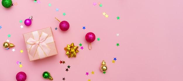Farbiger schneeflocken-süßigkeitsstern und geschenkbox mit band auf rosa hintergrund ist eine dekorative geschenkbox f...