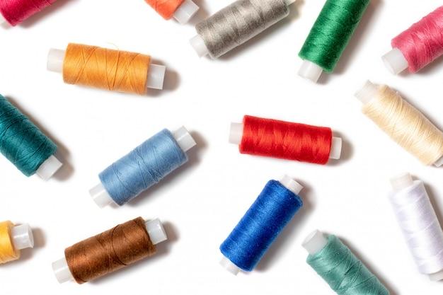 Farbiger thread umwickelt auf weißem hintergrund, nähendem, handgemachtem und diy-konzept