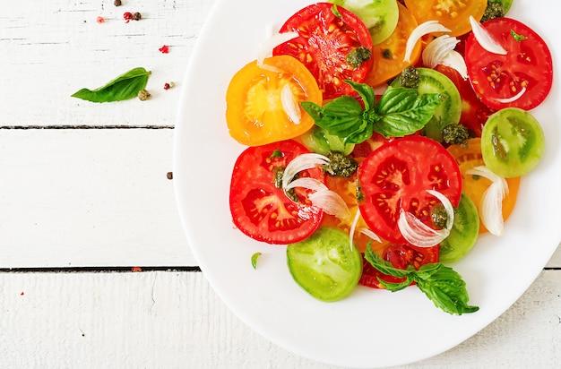 Farbiger tomatensalat mit zwiebel und basilikum pesto. veganes essen. ansicht von oben. flach liegen