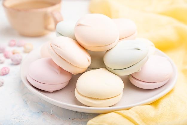 Farbiger zephyr oder marshmallow mit tasse kaffee und dragees auf weißem betontisch und gelbem textil. seitenansicht, nahaufnahme.