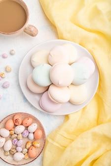 Farbiger zephyr oder marshmallow mit tasse kaffee und dragees auf weißer betonoberfläche und gelbem textil