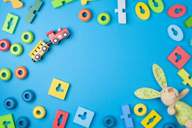 Farbiges holzspielzeug, hase und ein zug auf blauem hintergrund. flach liegen. draufsicht. platz für text