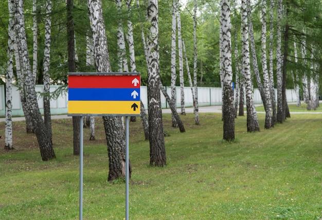 Farbiges leeres schild im park auf einem hintergrund von bäumen