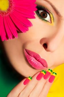 Farbiges make-up und mehrfarbige french manicure mit gerbera